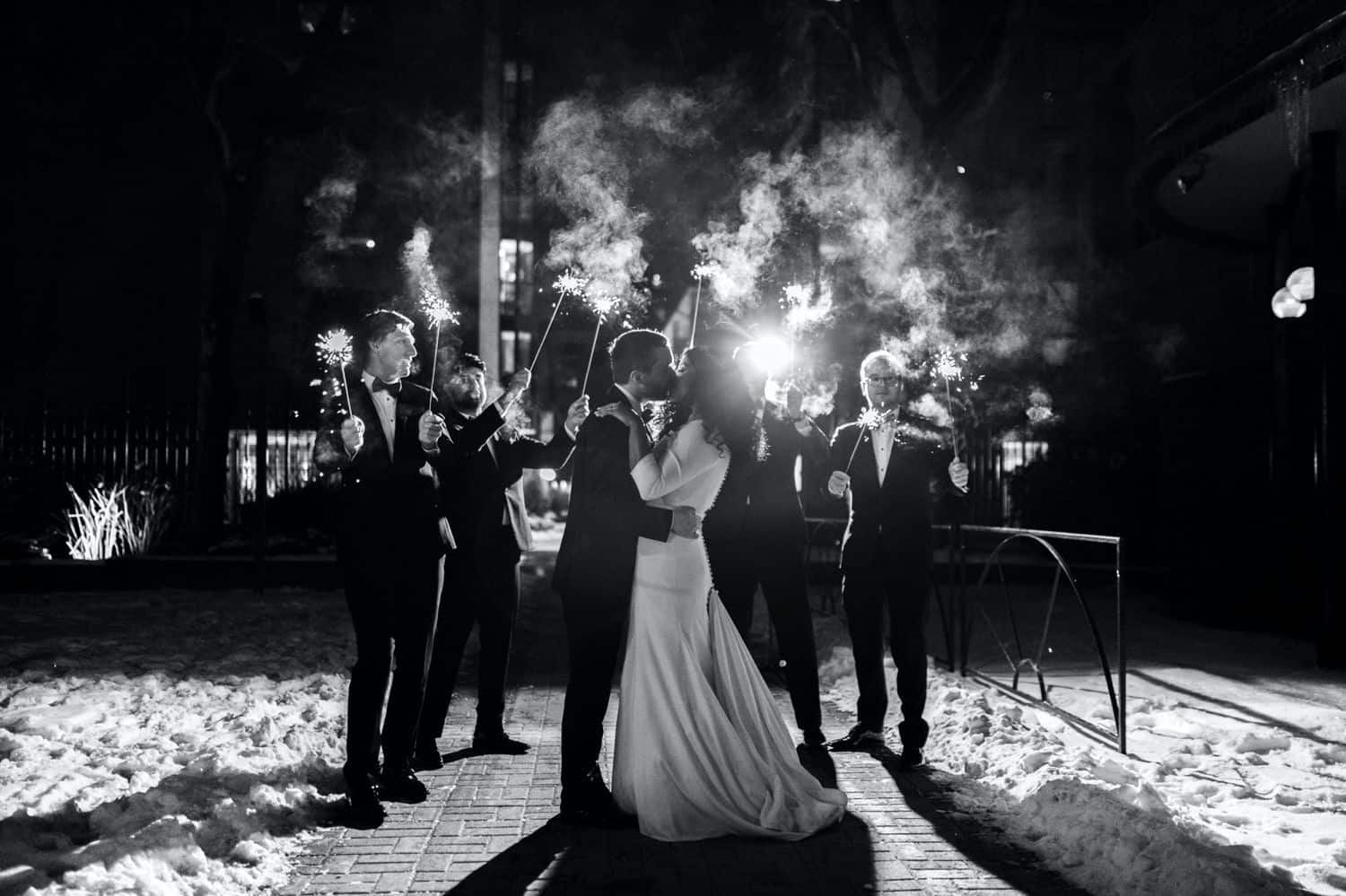 A bride and groom kiss as their wedding party waves sparklers at night