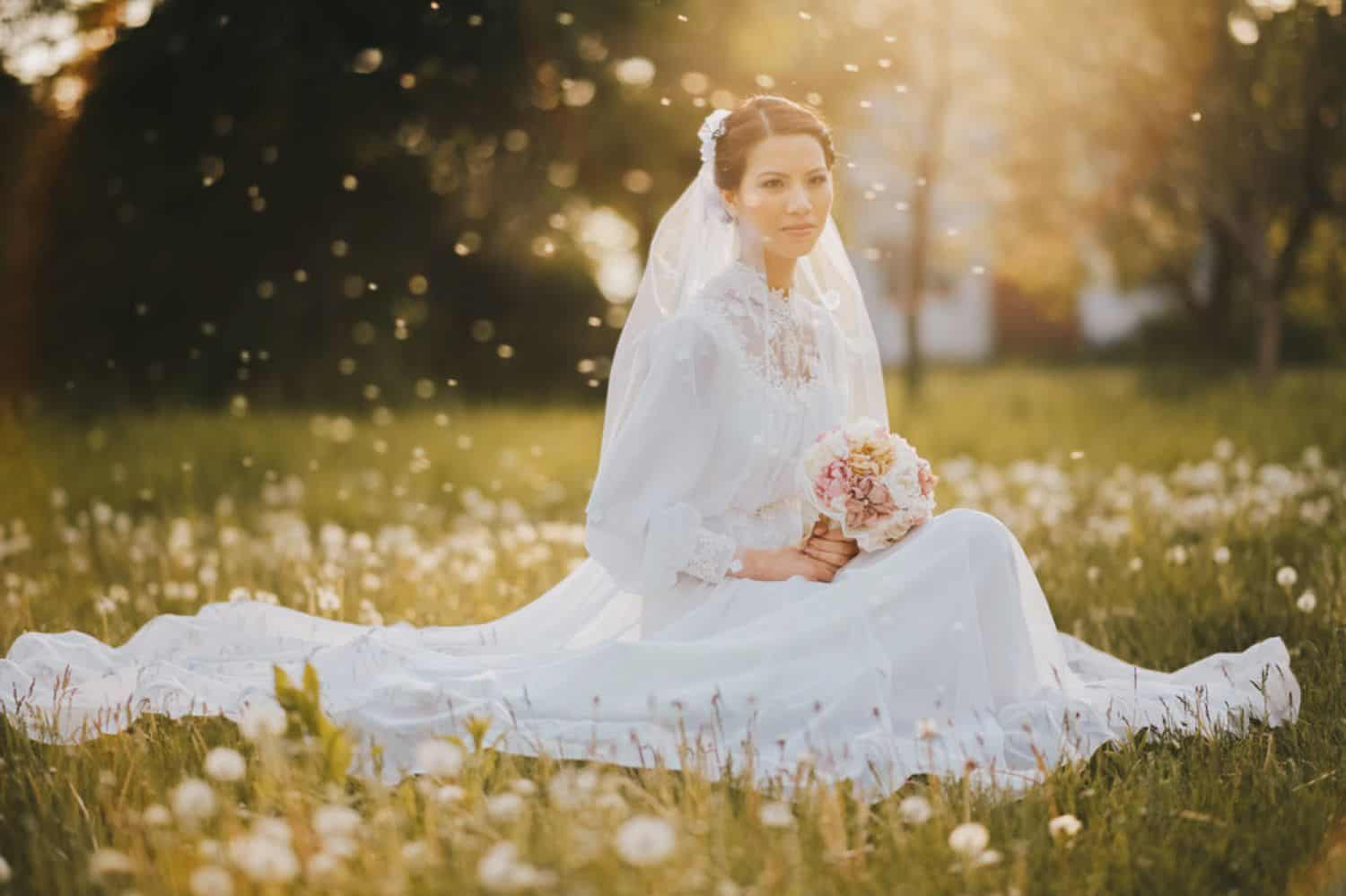 A bride kneels in a field for a sunset portrait