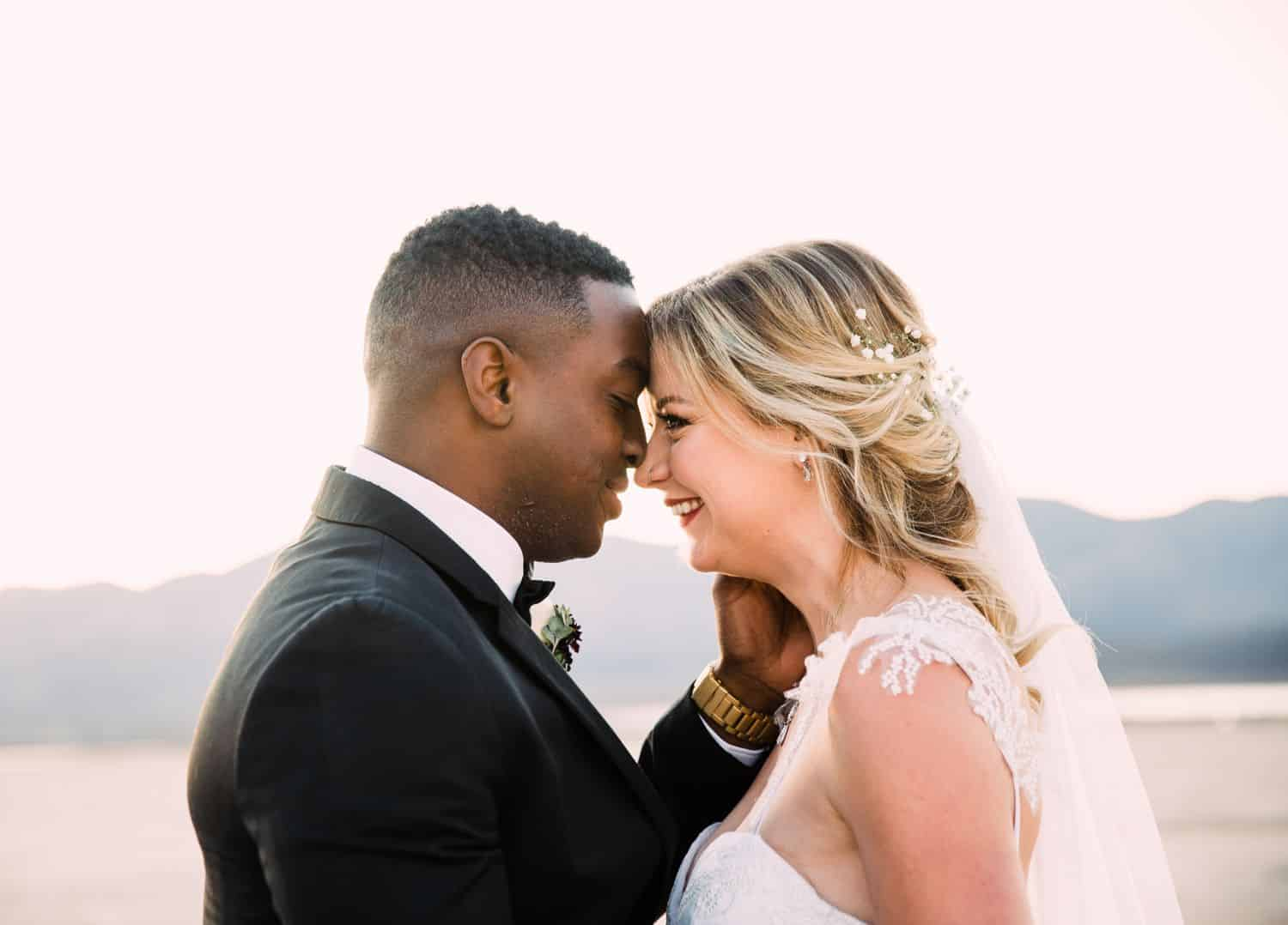 A bride and groom pose nose-to-nose while smiling for portraits after their desert wedding