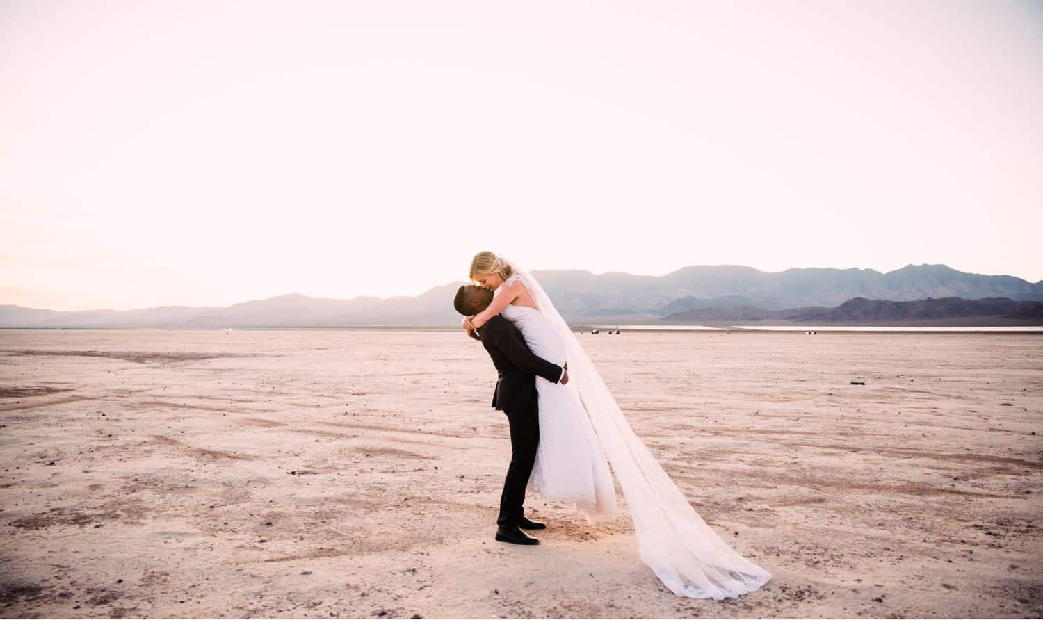 The groom lifts his bride into the air for a kiss after their desert ceremony