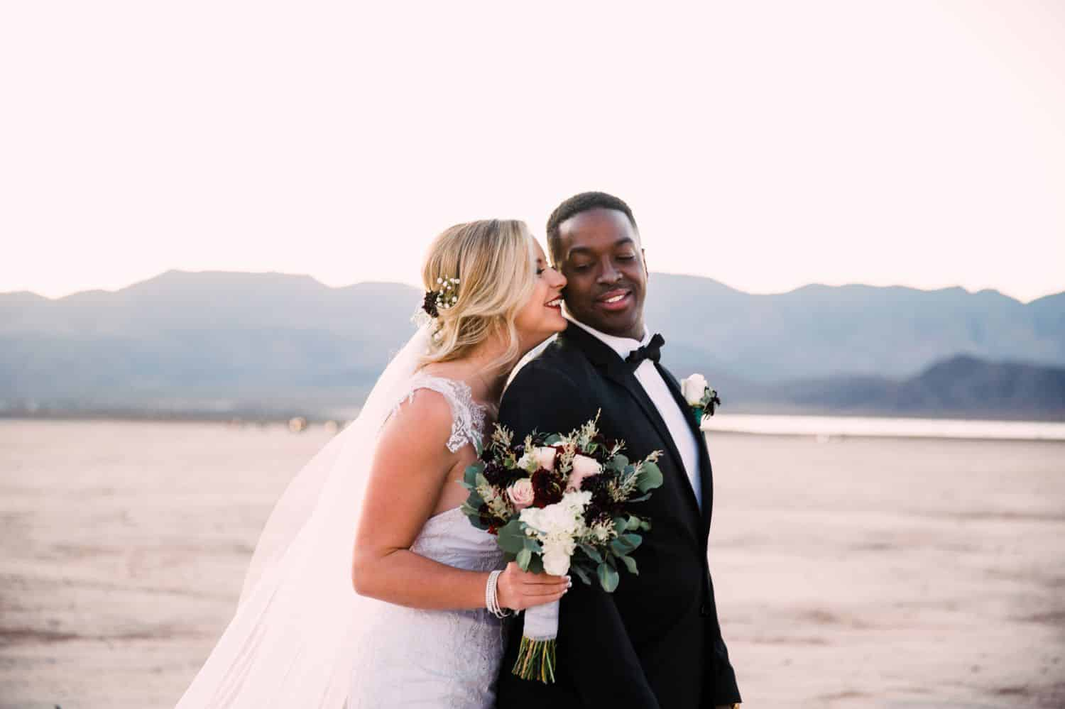 A bride stands behind the groom and kisses him on the cheek during their desert wedding