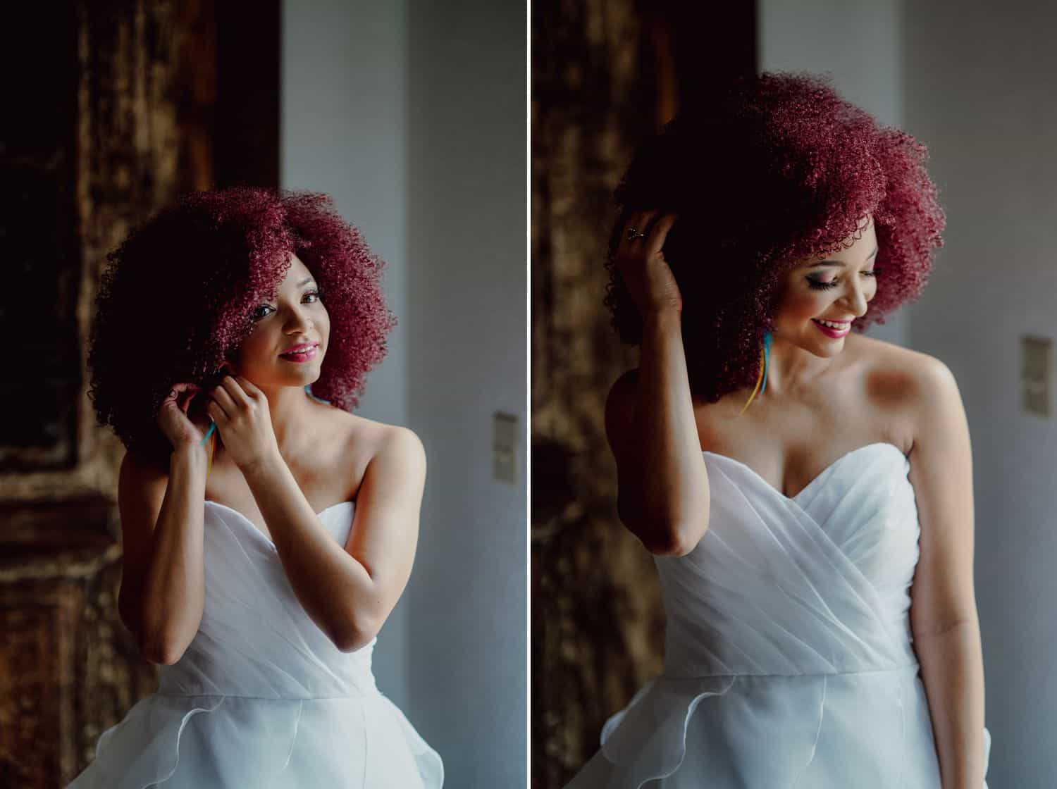 A Black bride with hot pink hair poses for a portrait while getting ready for her wedding