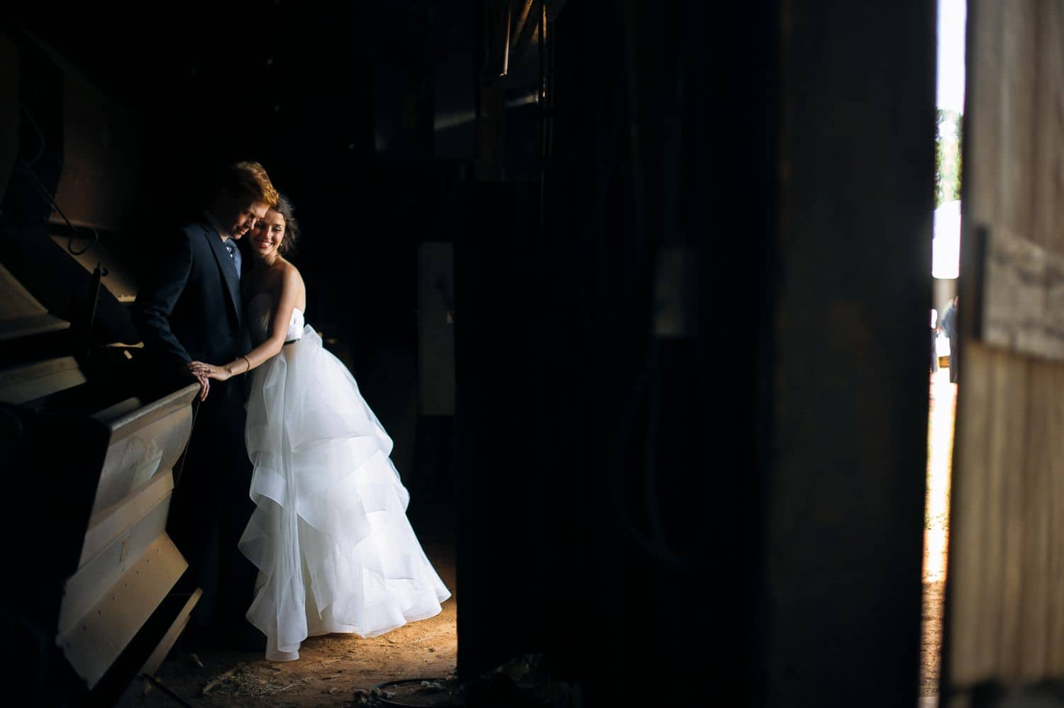A photographer sneaks a quick photo of a bride and groom having an intimate moment on their wedding day
