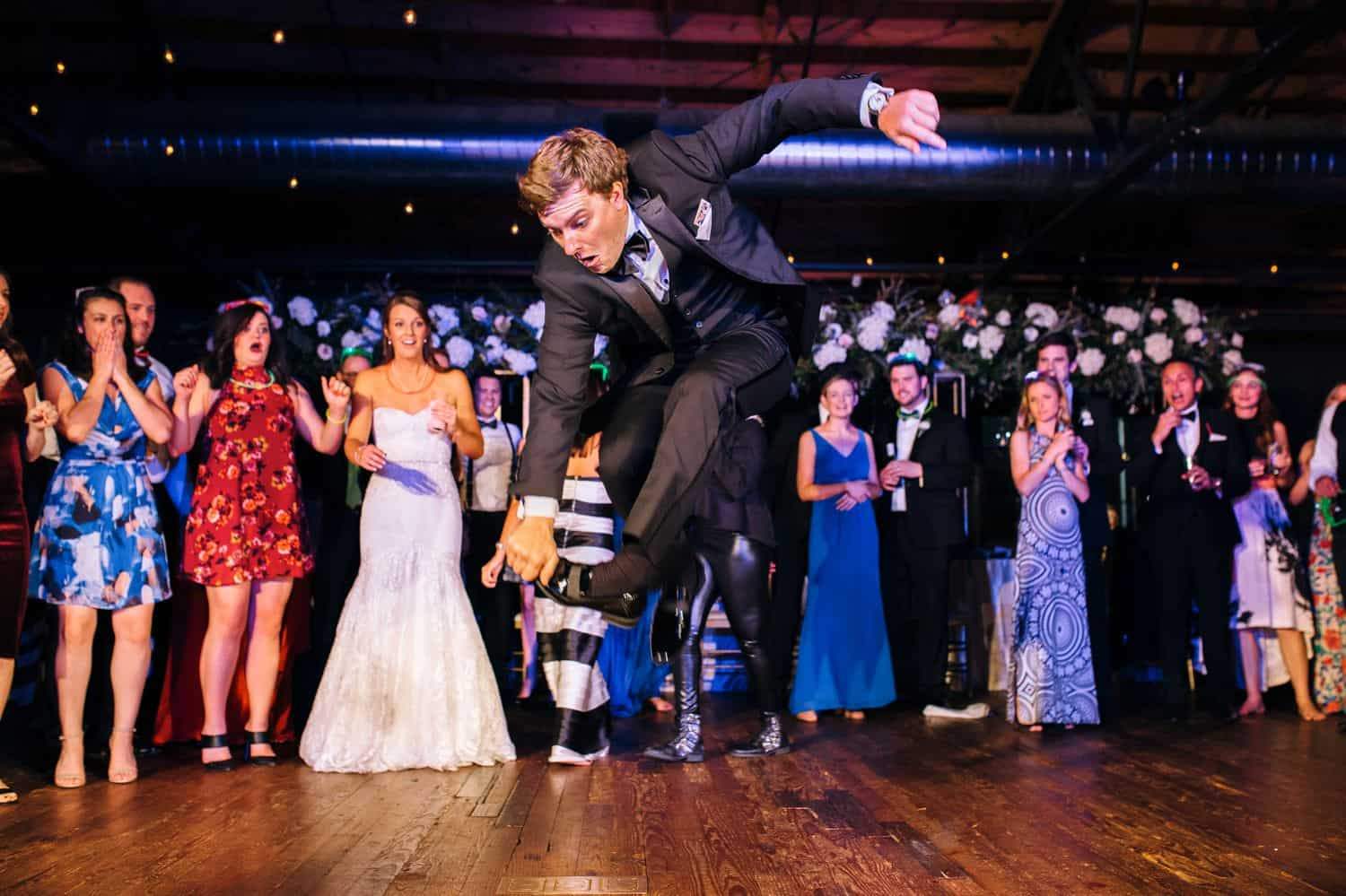 A groomsman leaps into the air in an impressive dance move during a wedding reception