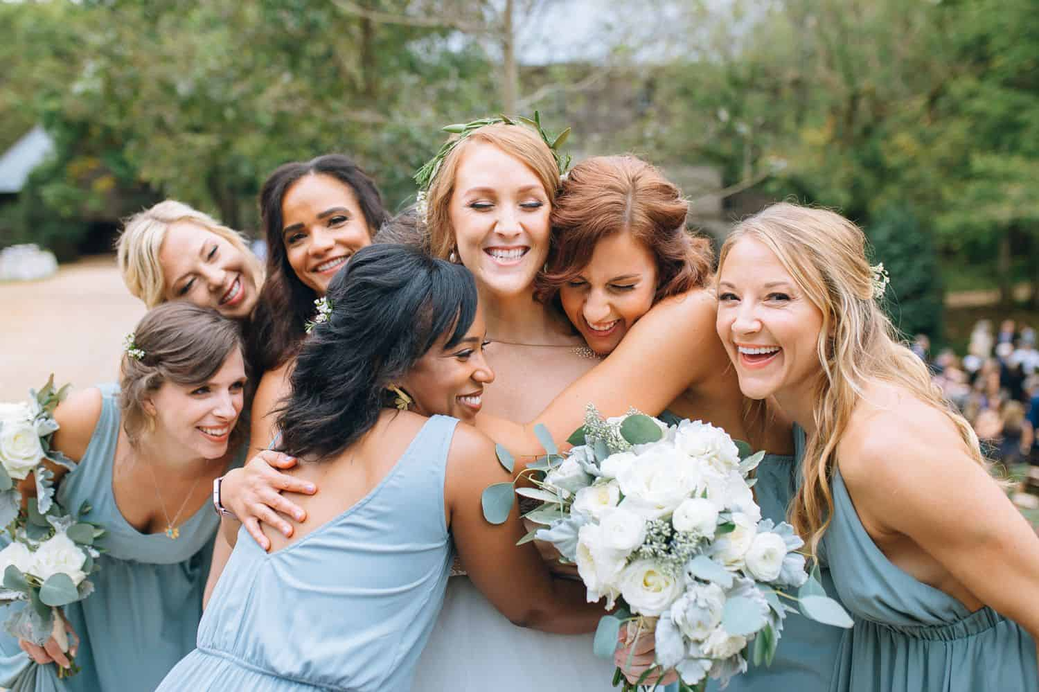 Bridesmaids in pale blue dresses gather around the bride for hugs on the wedding day