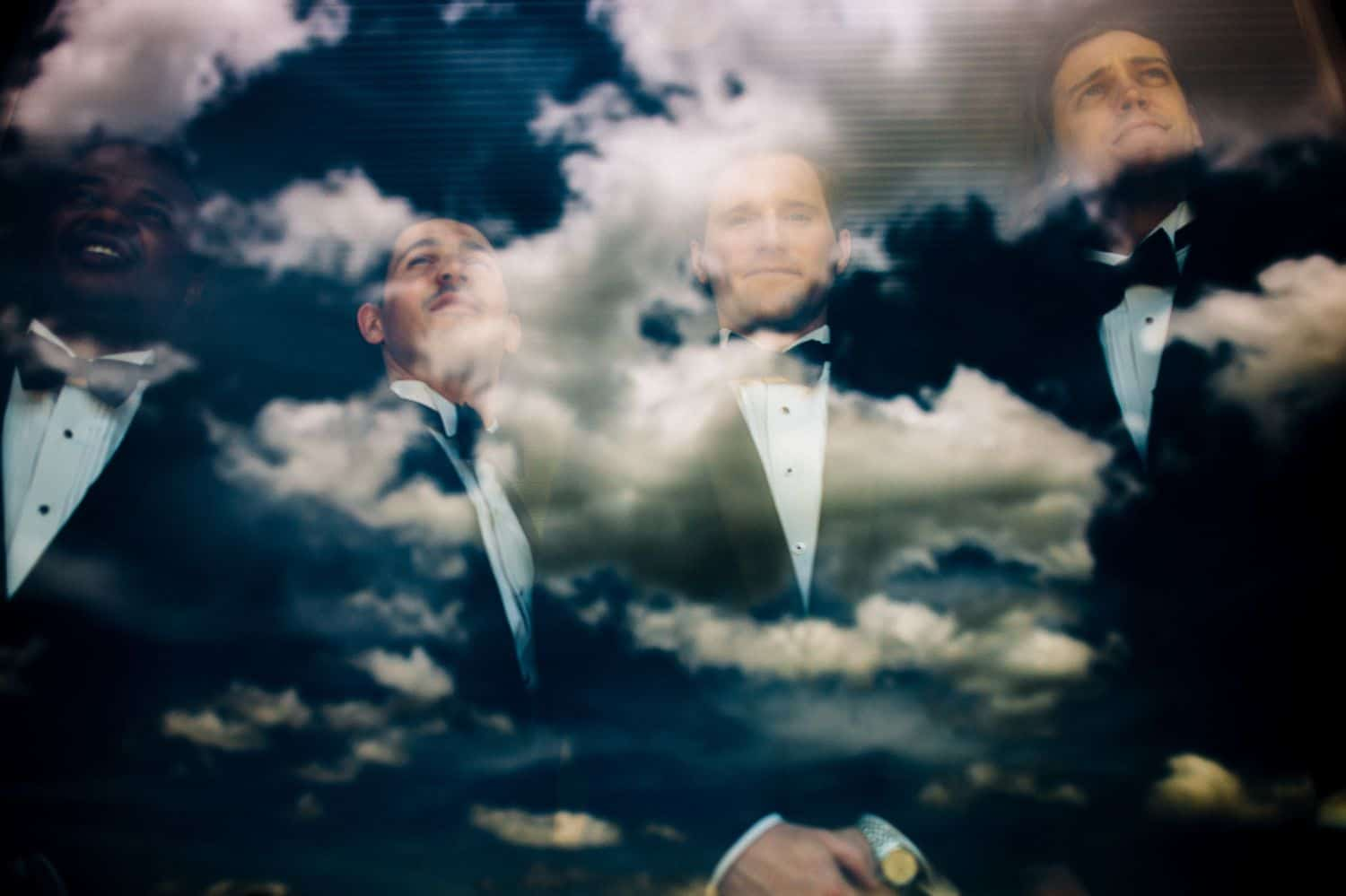 A groom and his groomsmen pose for a double exposure portrait with a deep blue cloudy sky