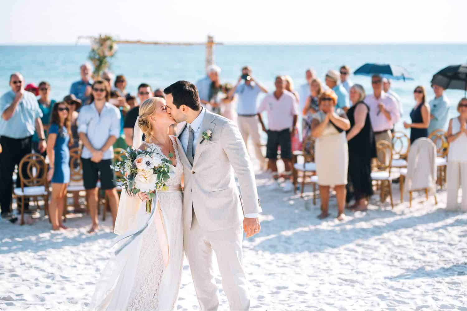 A bride and groom kiss after processing up the aisle after their wedding ceremony on the beach