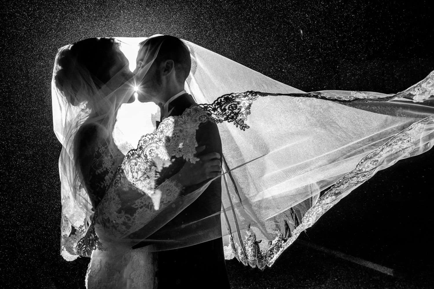 A bride's veil covers her head as well as the groom's as they pose nose-to-nose for a backlit nighttime wedding portrait