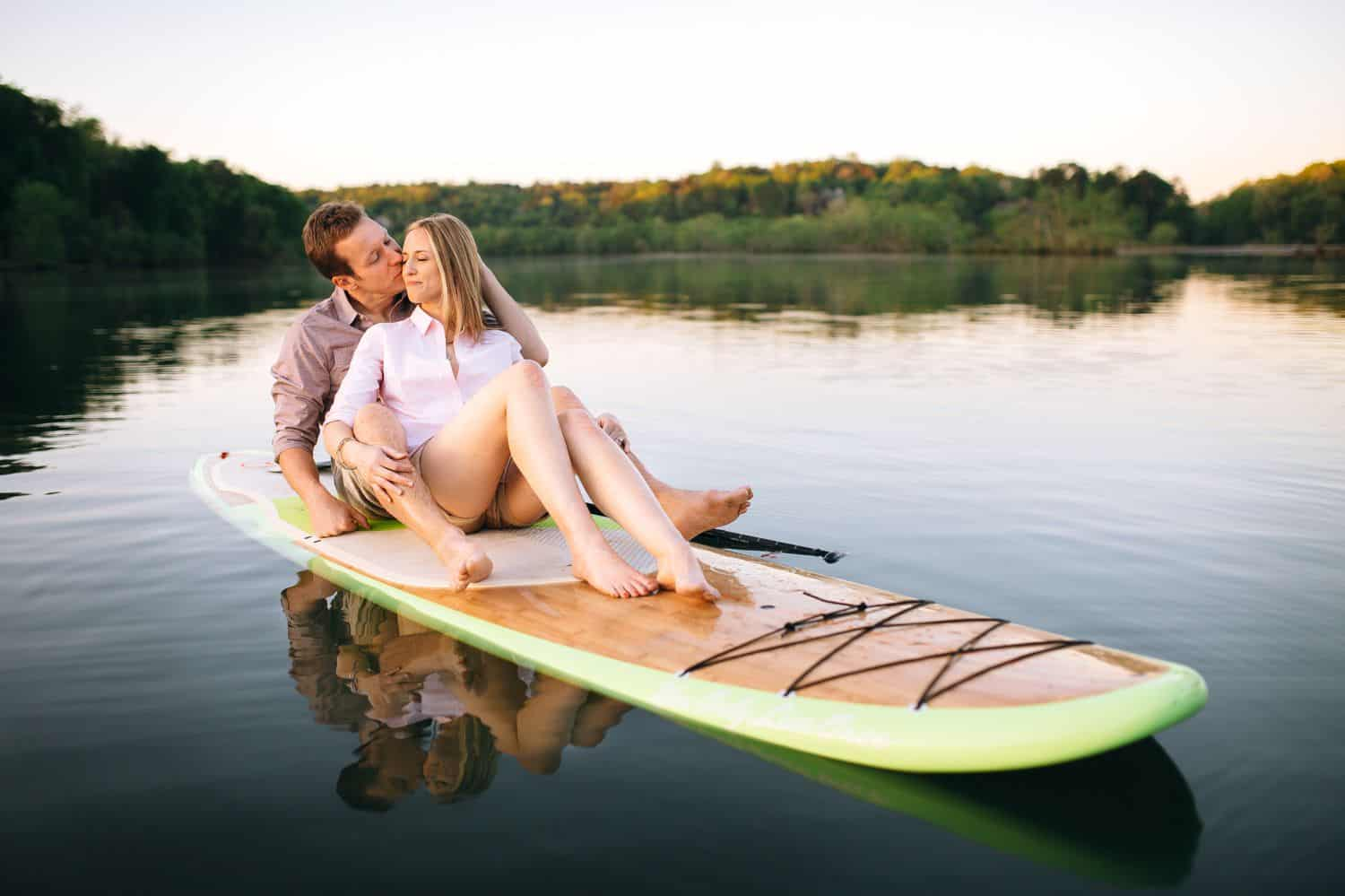 A couple sits on a paddleboard for their engagement photos