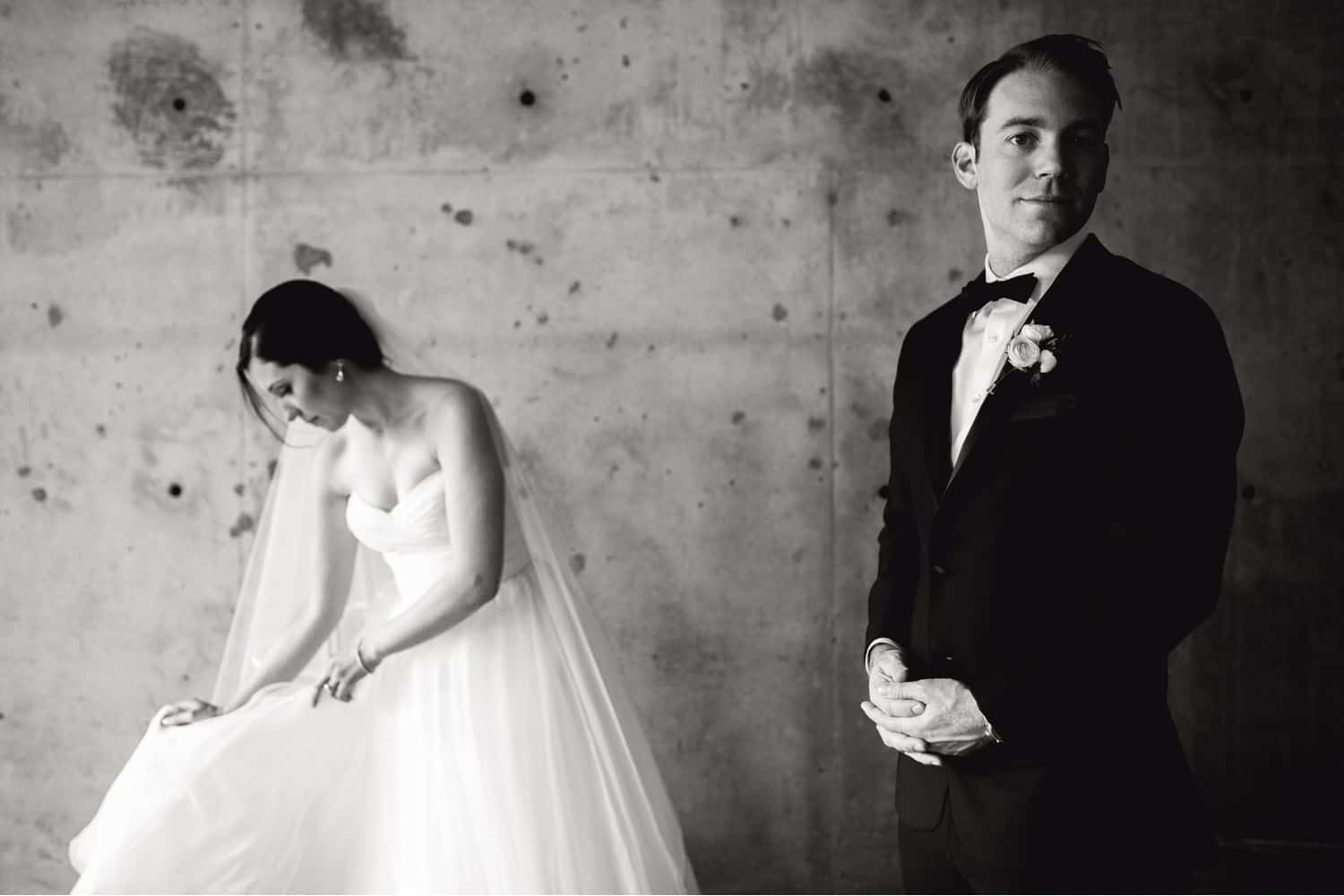 A bride adjusts her train as the groom glances at the camera in this black and white portrait from their wedding day