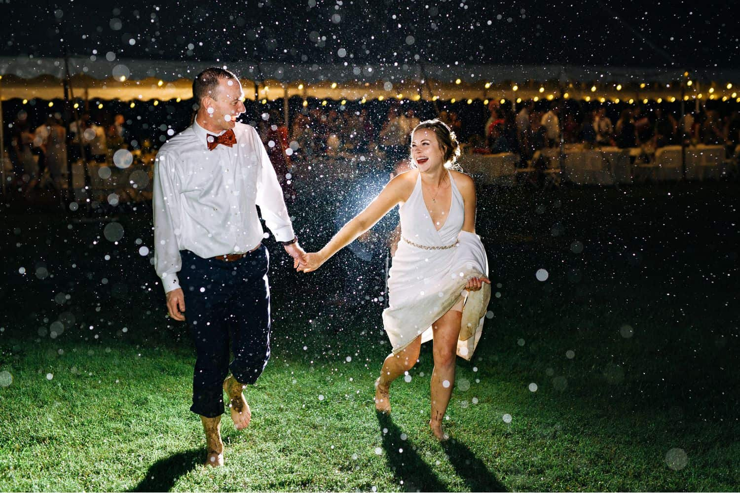 A bride and groom run through the rain at the end of their wedding reception