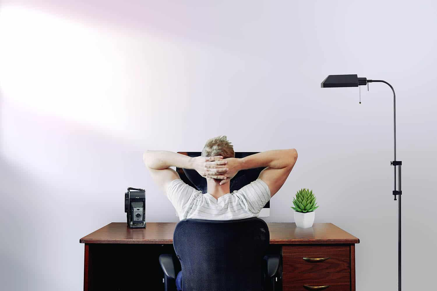 A white man in a white t-shirt sits at his desk in front of a white wall. He's looking at his computer monitor with his hands folded behind his head. He's learning to batch edit in Lightroom.