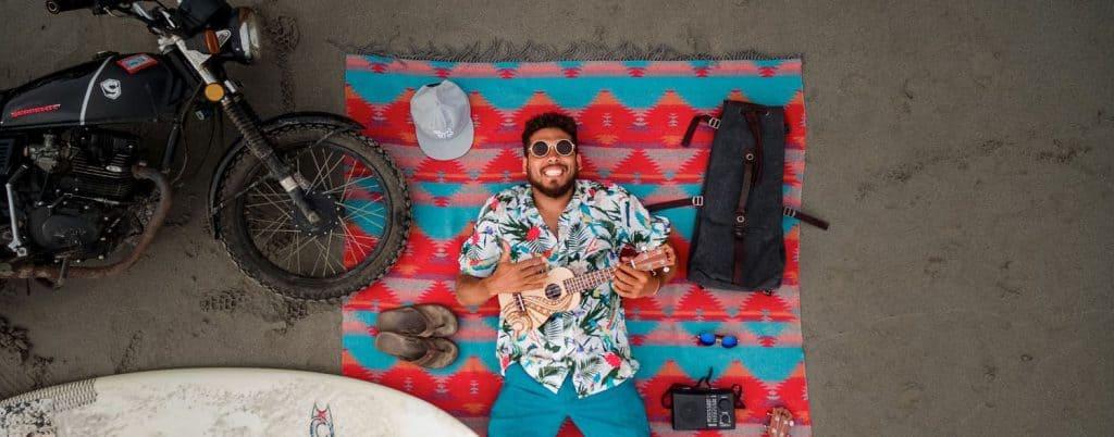 A man playing ukulele while lying on the sand
