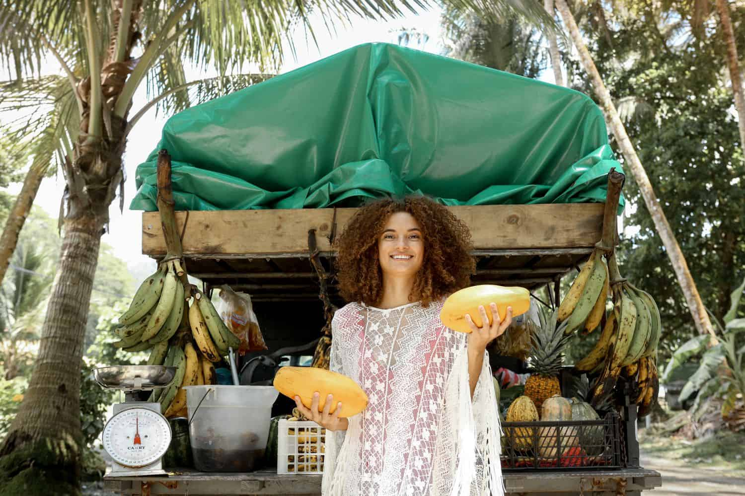 A woman posing in front of a fruit stand