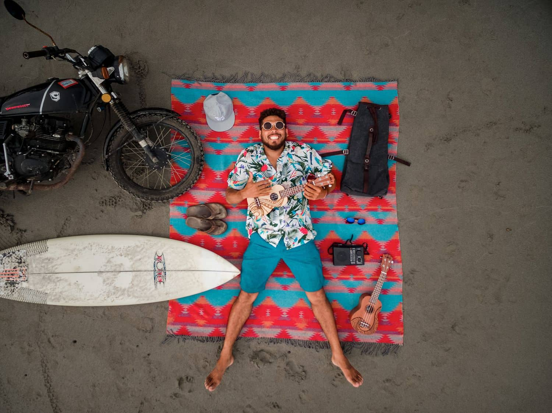 A man playing ukulele while lying on the beach