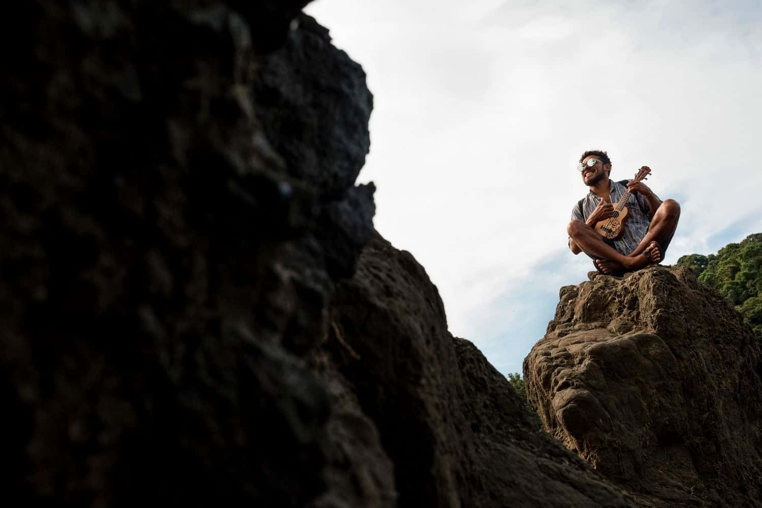 A man sitting on top of a large boulder while playing his ukulele