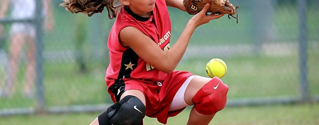 A young girl playing softball