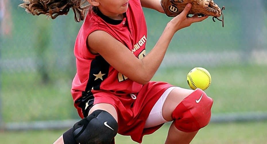 A young girl playing softball