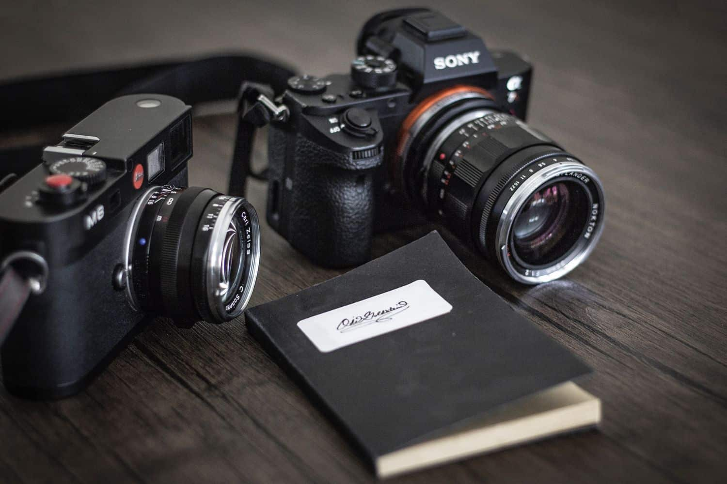 Two cameras and a black notebook placed on wooden surface