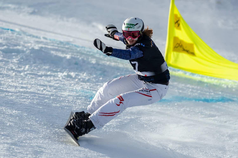 A woman snowboarding down a hill