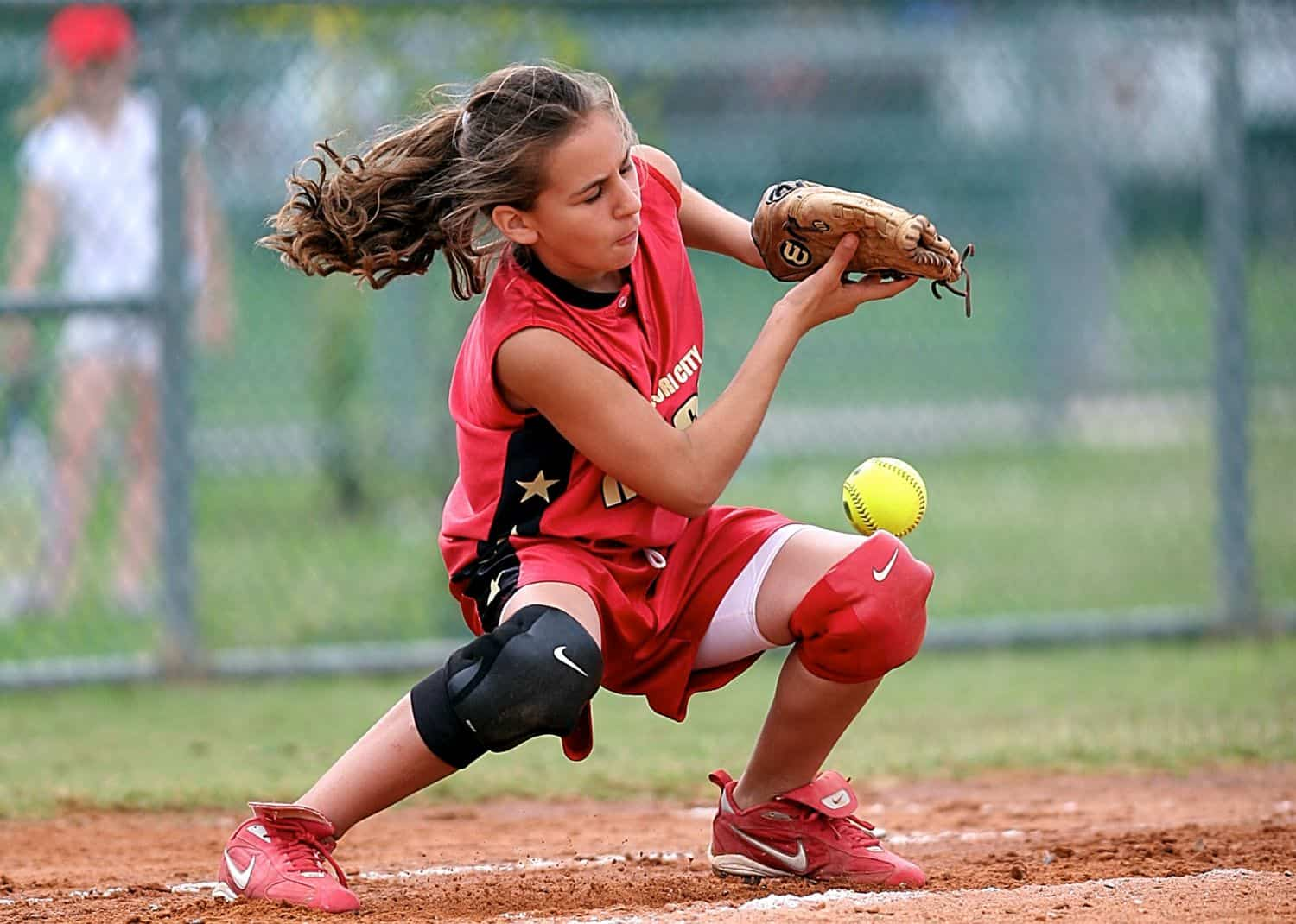A young girl wearing a red jersey catching a softball