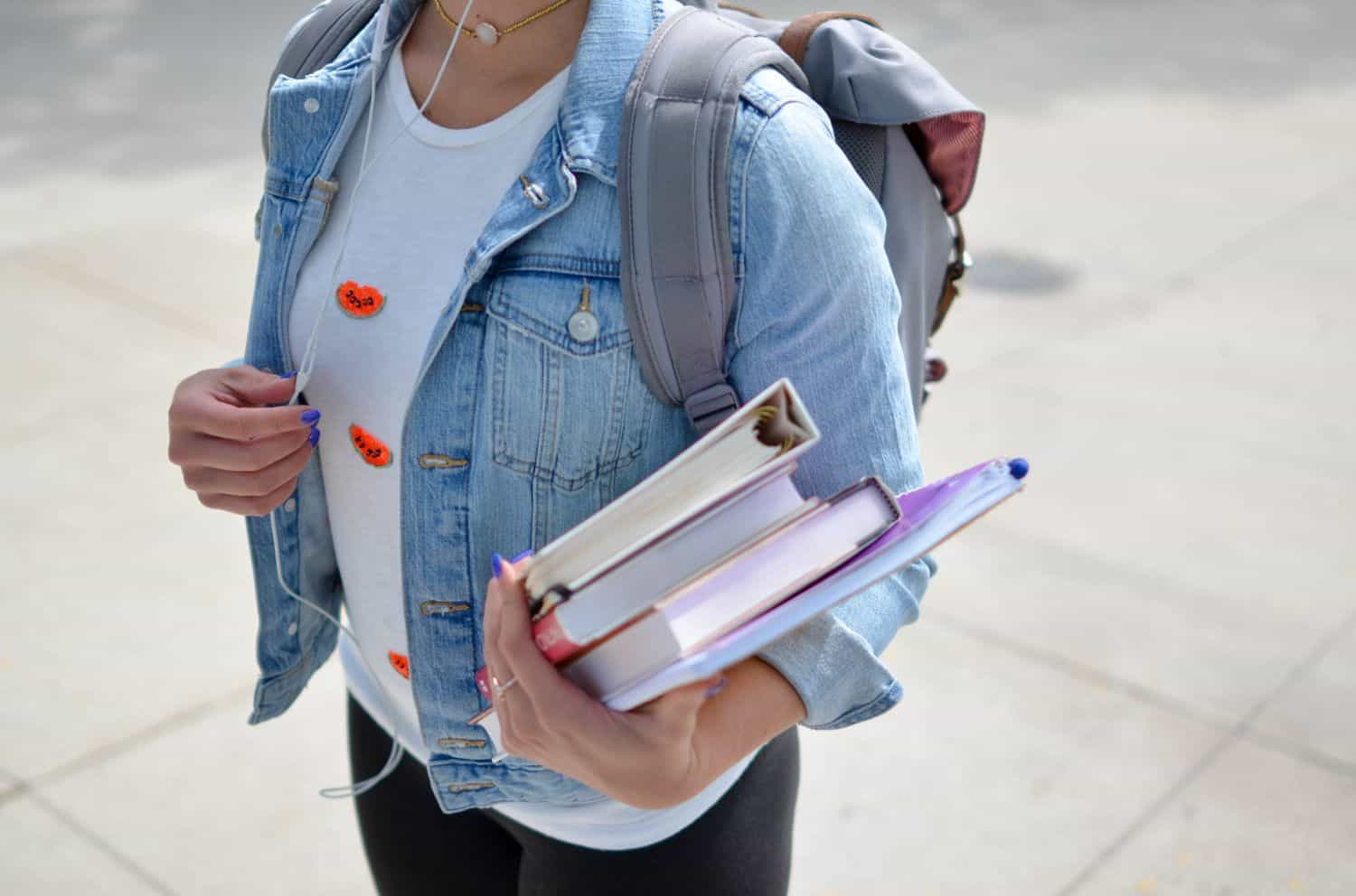 A student carrying her backpack and books while listening to music