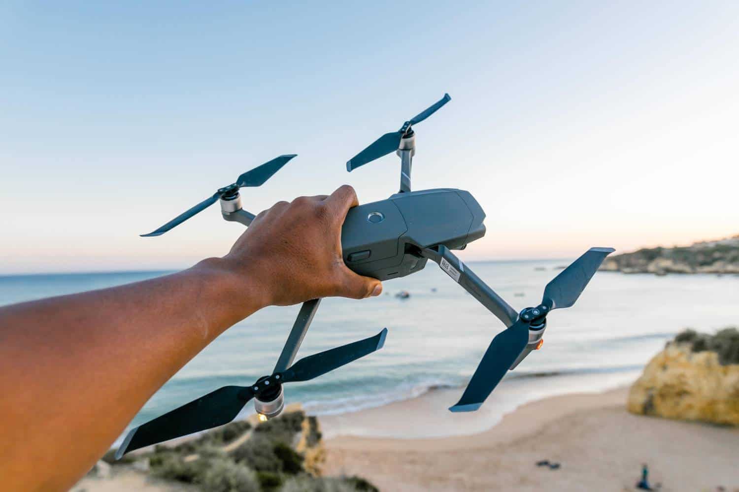 A hand is pictured holding a large drone camera in front of a beautiful ocean during a shoot by Humphrey Muleba