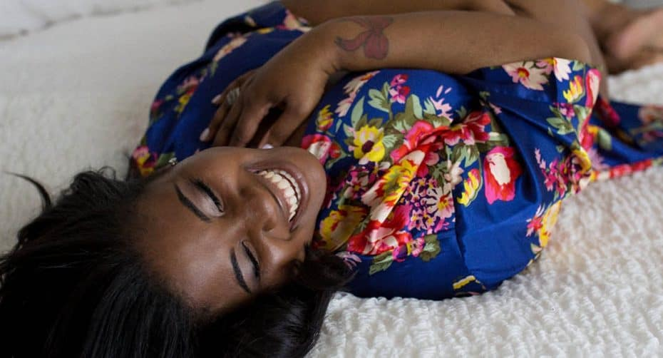 A smiling Black woman lies on a white bed in a blue floral robe for her boudoir session with Kinzie Ferguson of the Empowerment Studio