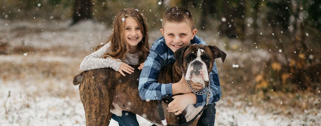 Two young children kneel in the snow with their arms around their dog, a boxer, who appears to smile at the camera. Christmas Mini Sessions: Ideas by Nicole Nero Photography