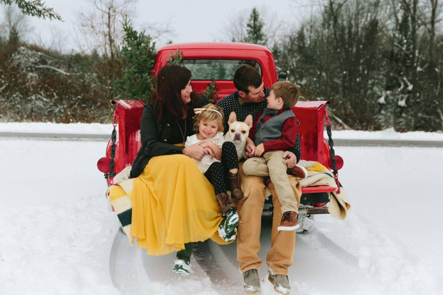 In this photo by Maine Tinker Photography, a mom, dad, two kids, and a small dog sit in the back of a vintage red truck that's parked in the snow. Christmas Mini Session: Ideas Families will ADORE!