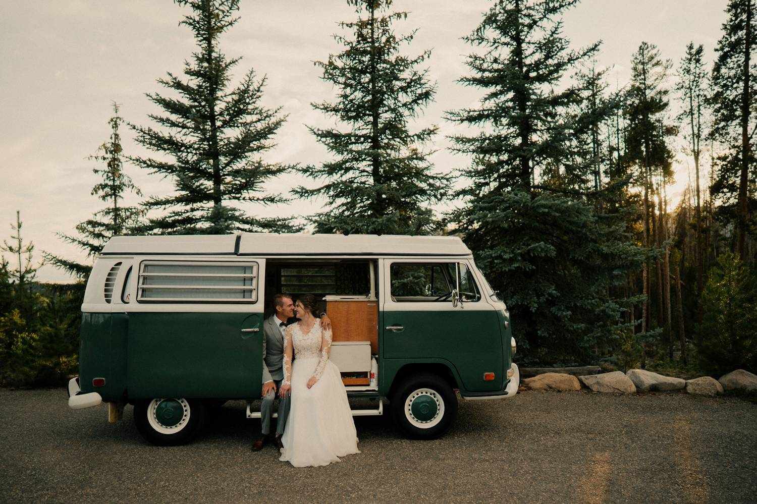 Customer Loyalty: By Nick Sparks, a camper van is parked in front of a stand of evergreens. A bride and groom sit in the open doorway.