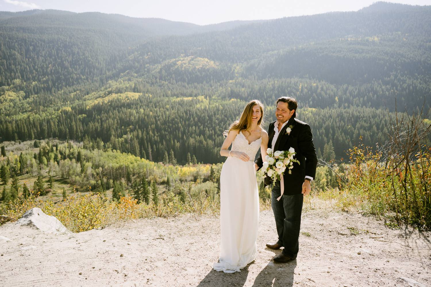 Customer Loyalty: By Nick Sparks, a bride and groom stand close together laughing as the Denver hills rise behind them.