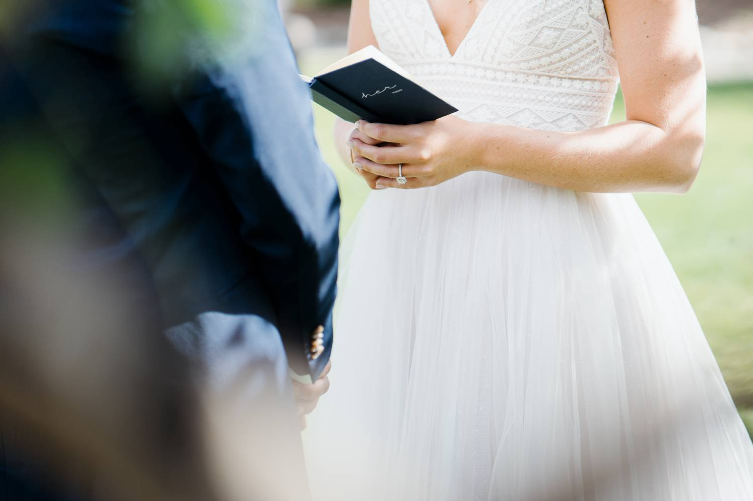 Customer Loyalty: By Nick Sparks, a mid-ceremony detail shot depicts a bride's hands holding her book of vows.