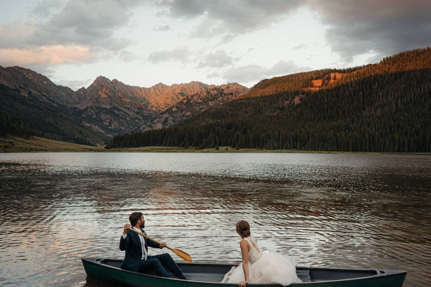Customer Loyalty: By Nick Sparks, a bride and groom row across a flat lake in the shadow of huge Colorado mountains.