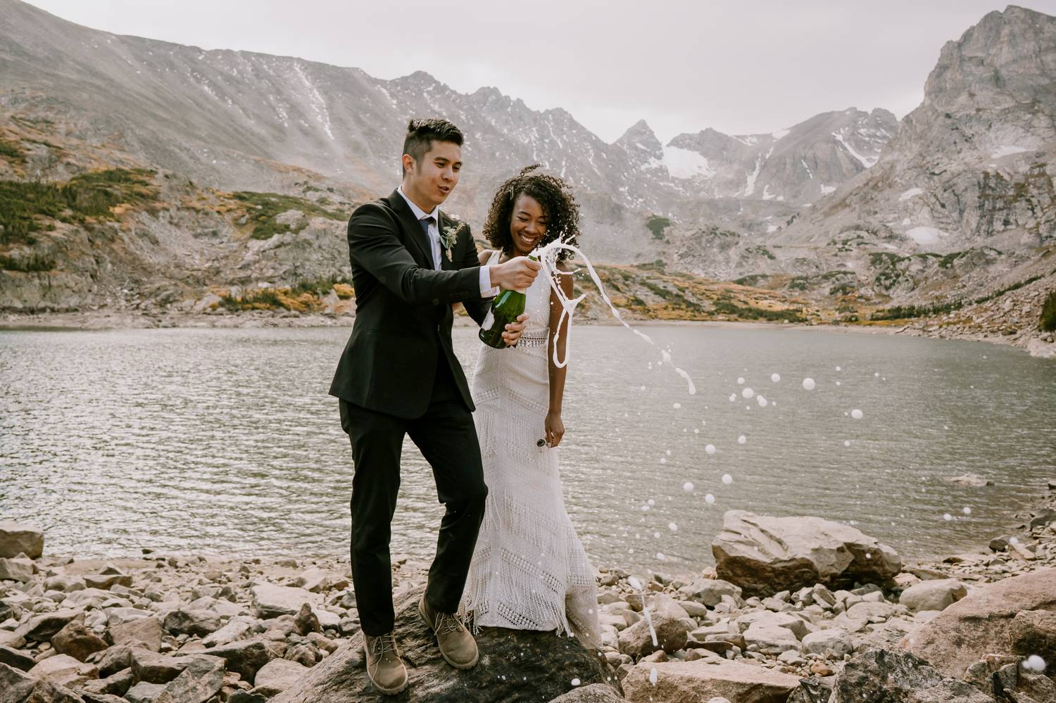 Customer Loyalty: By Nick Sparks, a bride and groom pop open a bottle of champagne beside a sparkling mountainside lake.