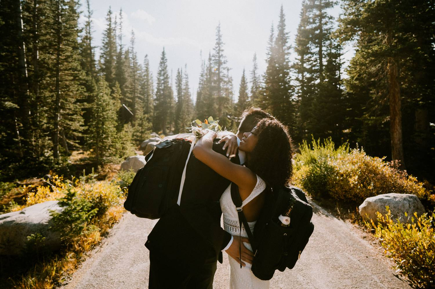 Customer Loyalty: By Nick Sparks, a bride and groom wearing backpacks hug in the middle of a mountain road with evergreens soaring behind them.