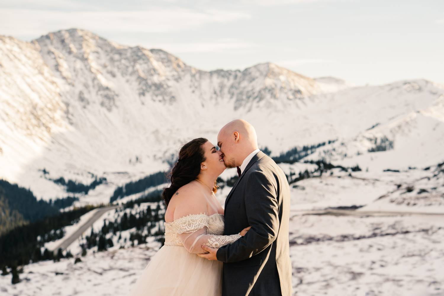 Customer Loyalty: By Nick Sparks, a bride and groom kiss in the foreground while the snowy Colorado mountains loom behind them.