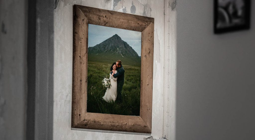 Photograph of a framed wedding photo hanging on a rustic wall in an old home. The photograph has stood the test of time, and remains as a beautiful memory for family and friends.