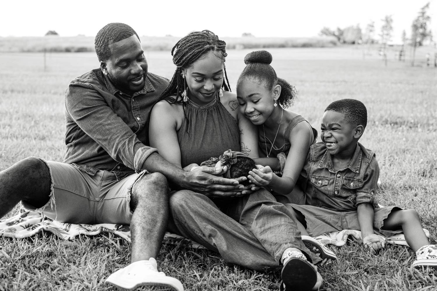 A smiling Black family sits on a quilt in a field with their hands collectively cradling the family's new baby.