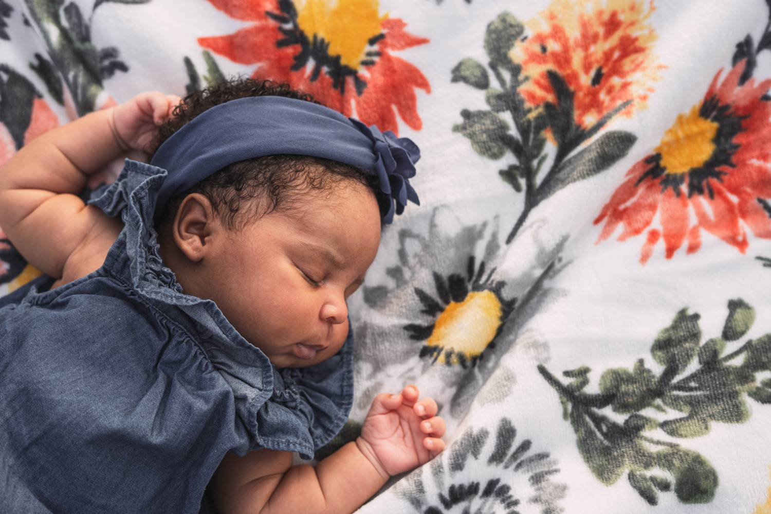 A newborn baby in a ruffled denim dress sleeps soundly on her back atop a colorful quilt.