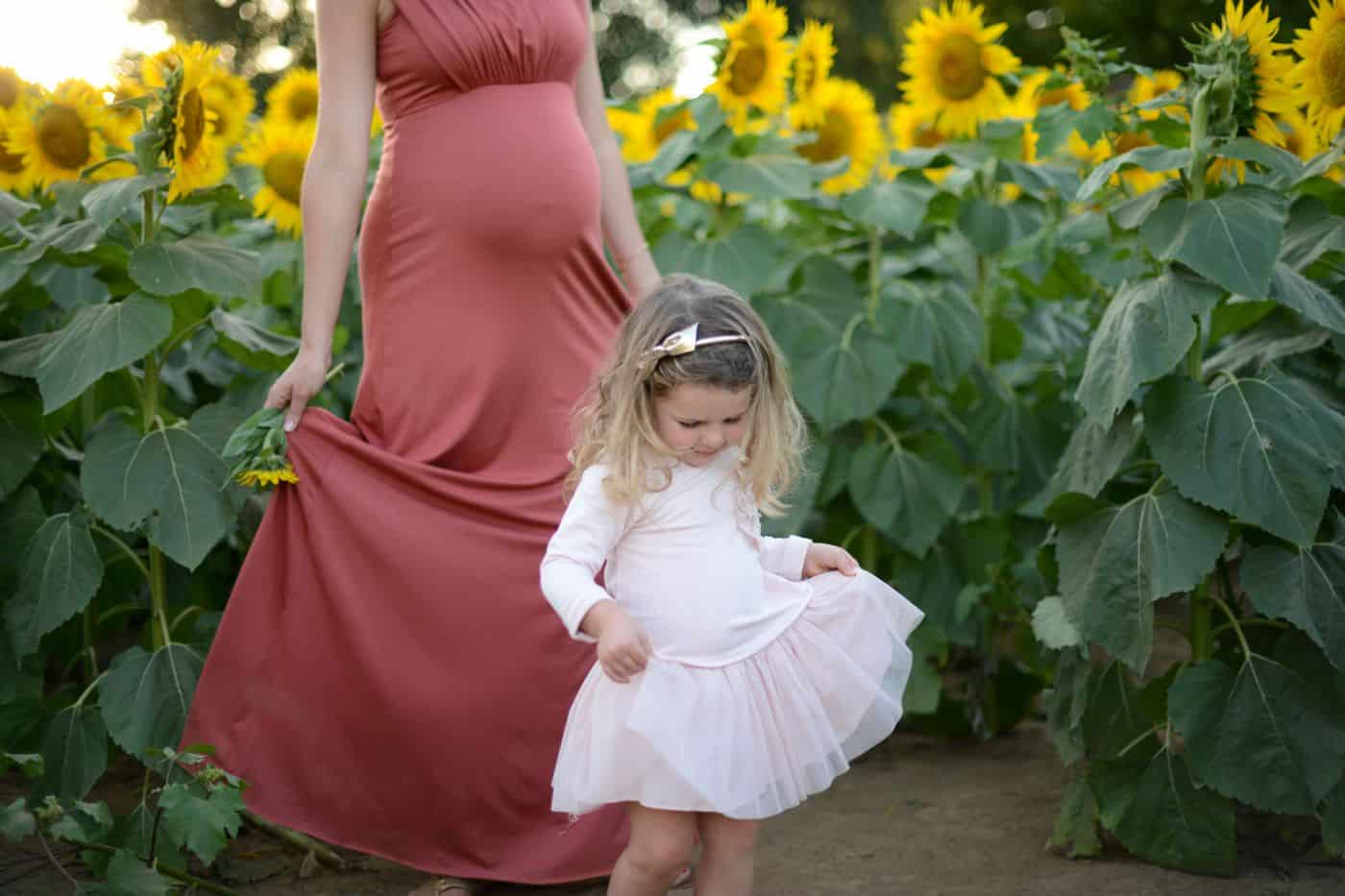 Andrea Nigh's maternity poses include an UNposing technique that allows for more natural images, like this photo of a pregnant mom and daughter dancing in a sunflower field.