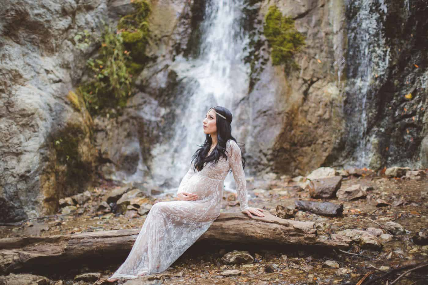Vanessa Hicks photographs a pregnant mother sitting on a log in front of a waterfall.