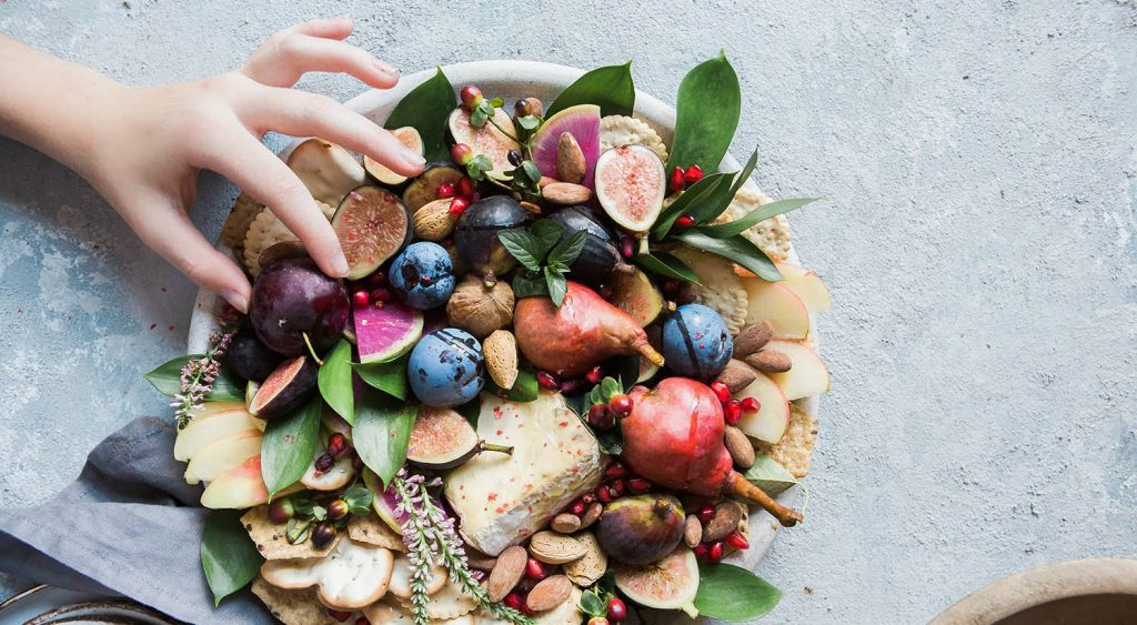 A hand is seen reaching for a berry on a plate of fruits, vegetables, and crackers, which is displayed on a concrete countertop.