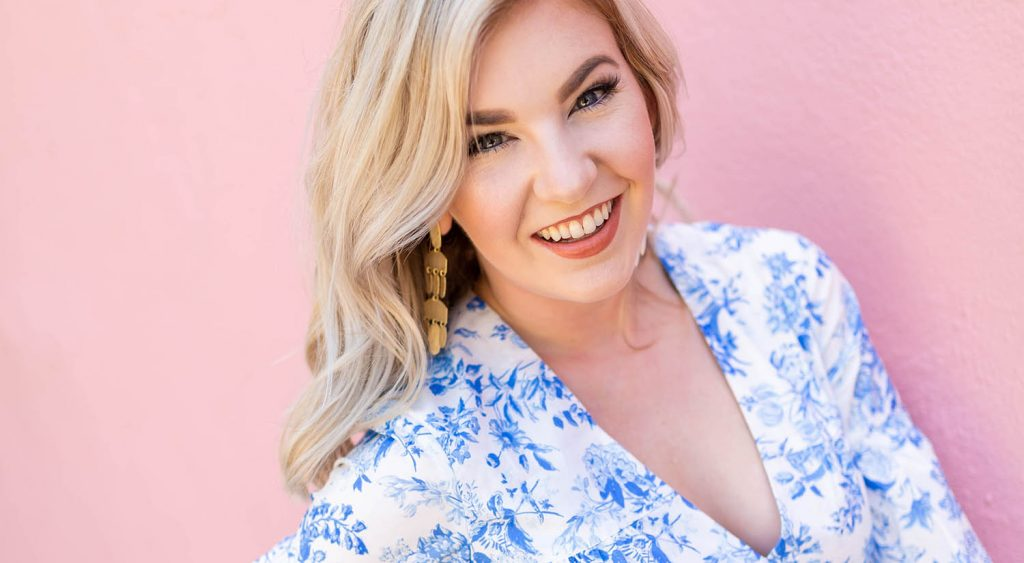 Headshot of Photographer Hope Taylor in a blue chintz dress against a pink wall for ShootProof's Find Your Focus podcast, episode 5