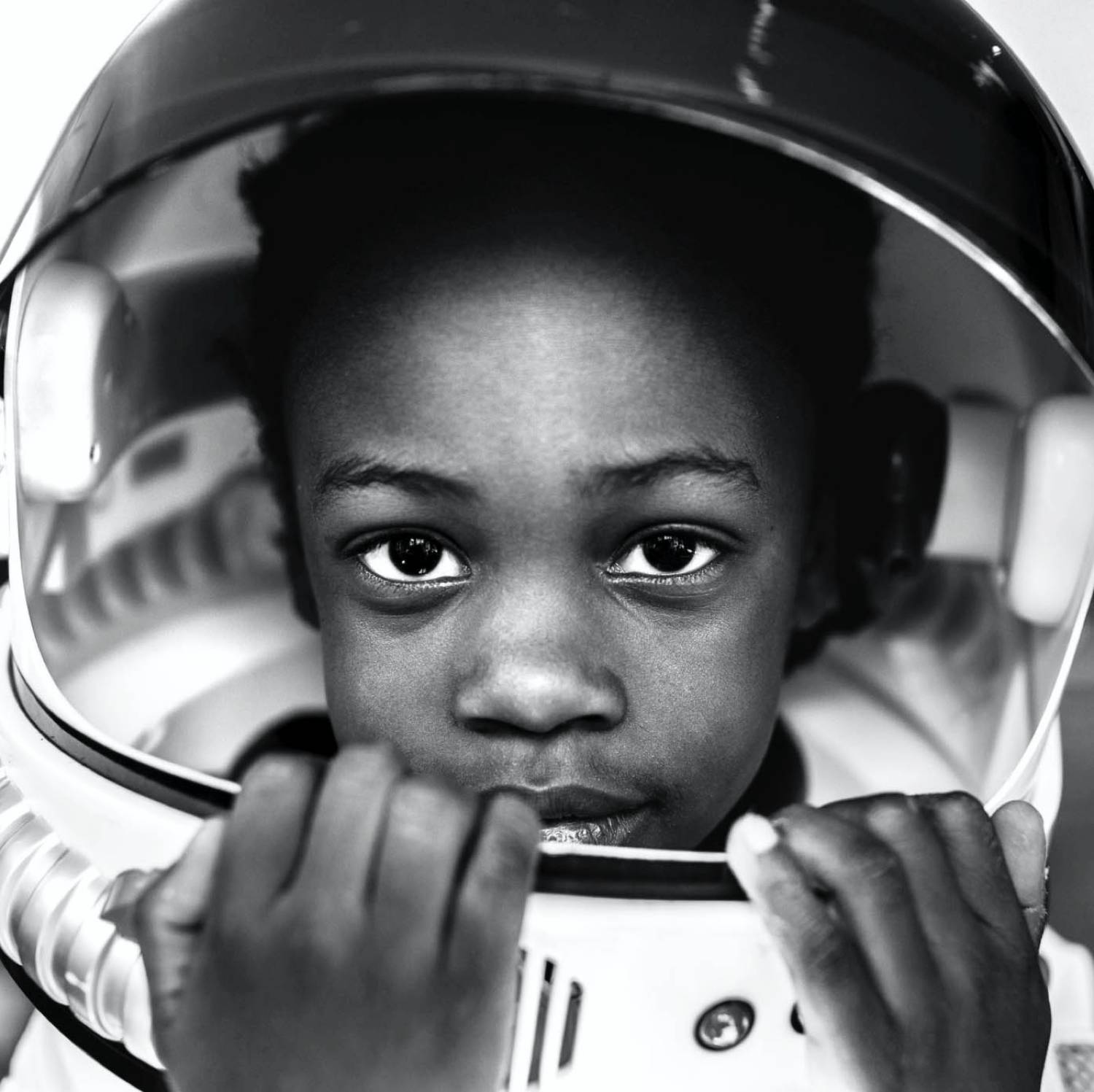 Adina Davis' black and white photo of a young Black child wearing an astronaut helmet.