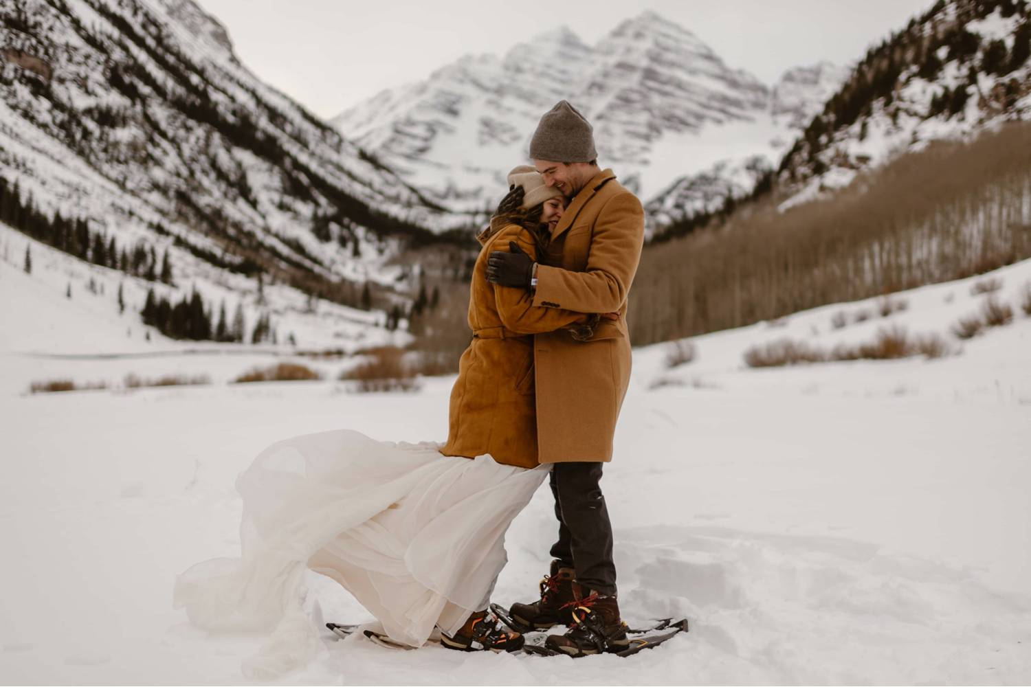 Adventure Instead's photo of newlyweds hugging in the snow. They're both wearing snow shoes.