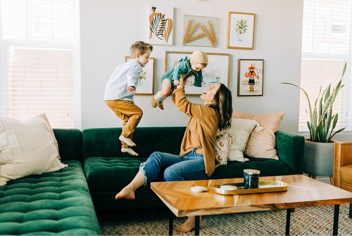 Photo: BreAnne Weston's lifestyle image shows a mom in a yellow shirt lifting her toddler daughter into the air as her young sun jumps on the green velvet sofa next to her.