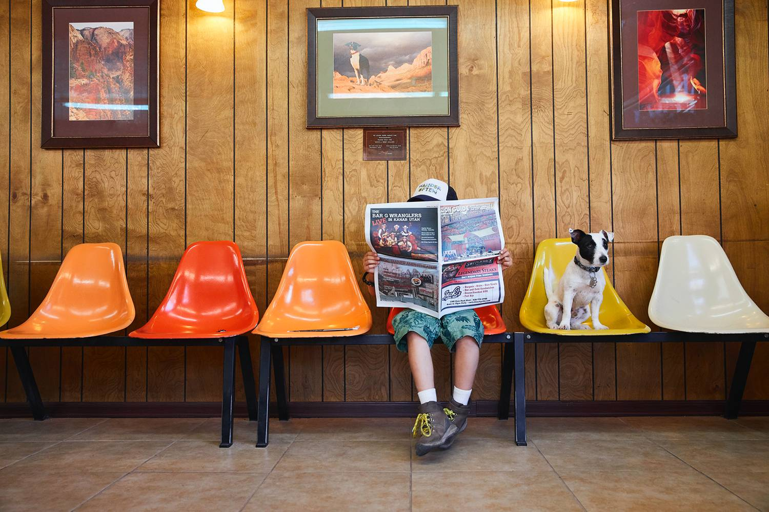 Photo: Candy Kennedy's documentary portrait shows a young boy sitting in a row of brightly colored chairs against a wood paneled wall. His face is shielded by the open newspaper he's holding. A small black and white dog sits in the chair next to him.