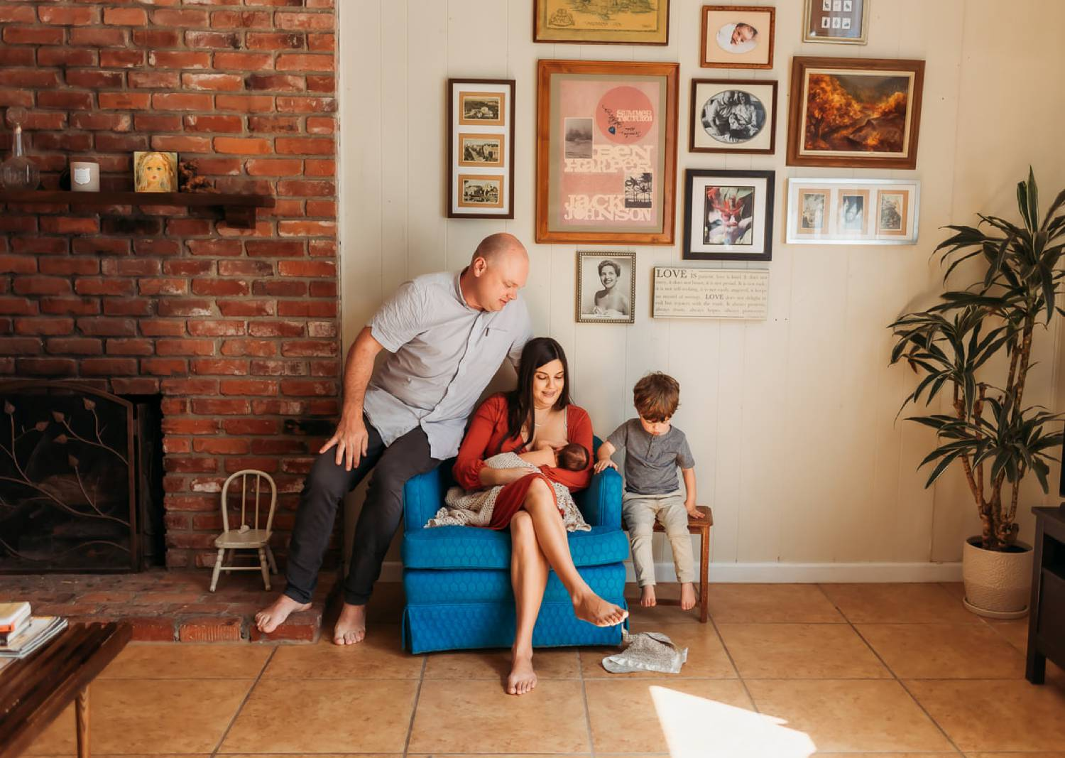 Photo: Charlotte Ani's in-home lifestyle newborn portrait depicts a mom sitting in a blue chair breastfeeding her infant. Her husband sits on the arm of the chair beside her, and their young son sits opposite his father on a small side table.