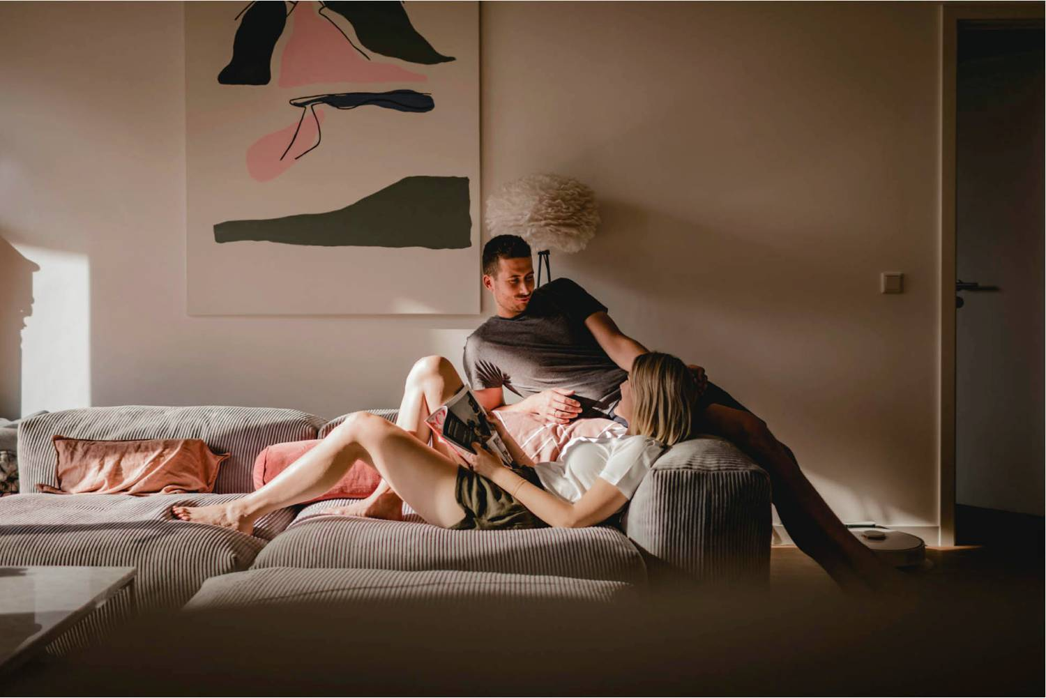 Photo: Diana Frohmueller's in-home lifestyle portrait of a couple depicts them reclining on a large gray sofa. An abstract painting hands on the wall behind them.